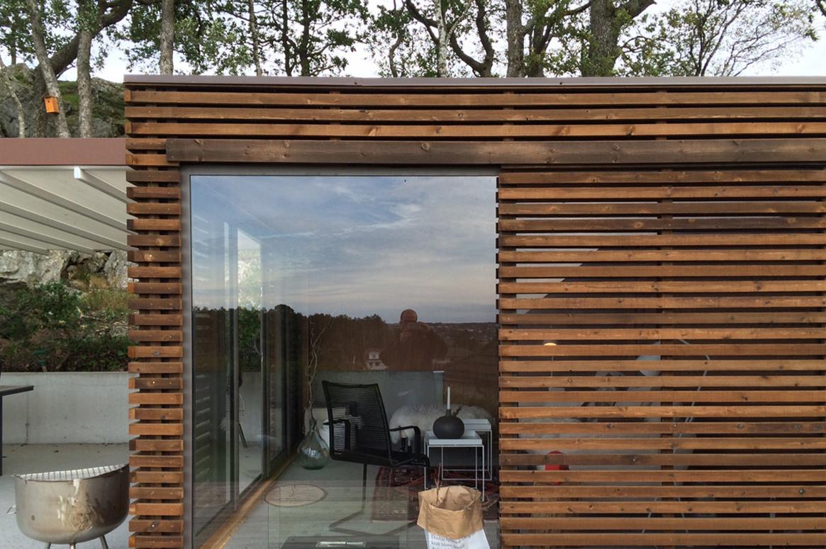 Hage Pavillion på Sandnes . Volumet for hagestuen er forsiktig plassert på kanten av betongplattingen. Den doble fasaden av glass og spiler gjør at hagestuen kan skjermes etter behov.