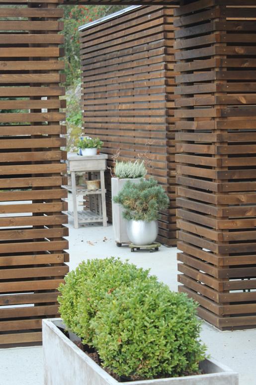 Hage Pavillion på Sandnes .Kjøkkenvolumet har flere funksjoner, såsom lysende lampe, oppbevaringsplass, port inn til spiseområdet og skaper grensen til spiseområdet. Hagedesign i Sandnes, Arkitekt i Sandnes.
