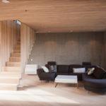 Stue. Eike spiller i himling. Bærende vegger i plate forskalt betong og eike gulv. Designed trapp hengende fra taket til andre etasje. Patio Hus i Sirevåg