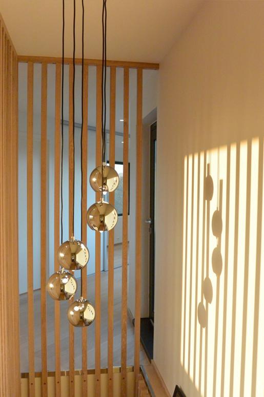 Eike spiller fortsetter til himling i andre etasje og danner rekkverk for trappen i andre etasje. Designet av arkitekt. Eik. Patio Hus i Sirevåg