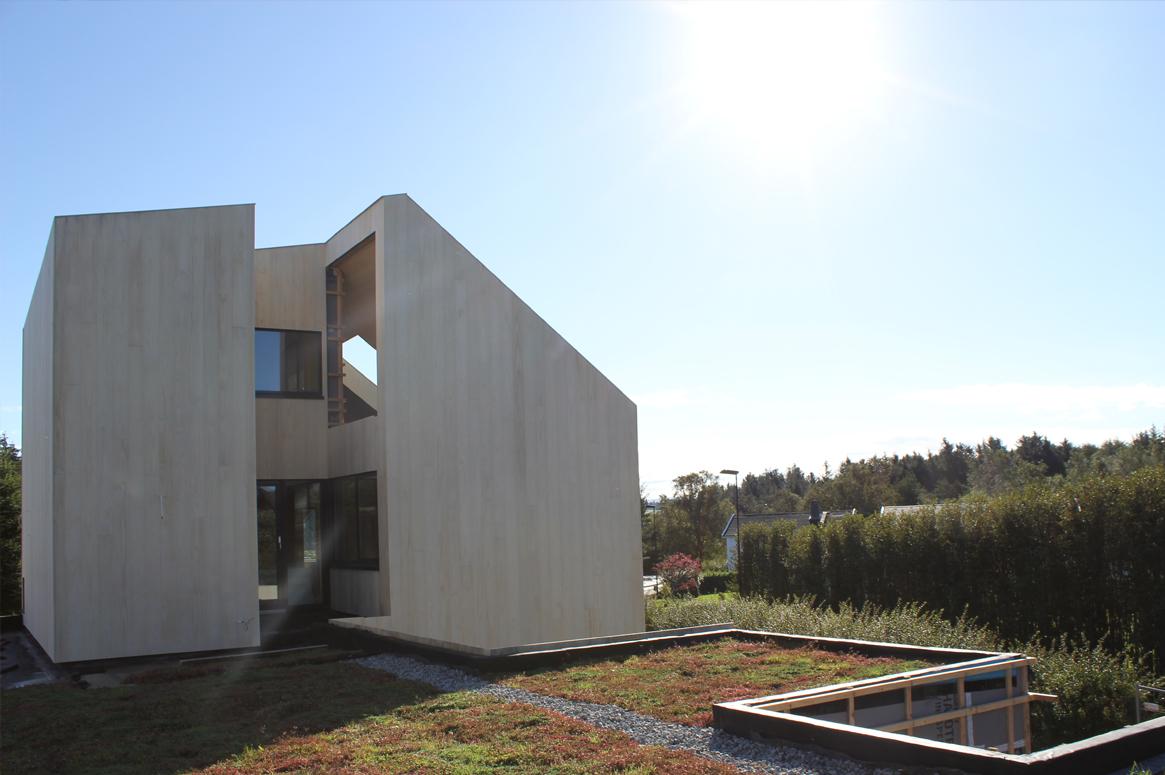 3 Patio Hus på Bryne. Sedum taket smelter sammen med omkringliggende vegetasjon. Tårnet fremstår som et abstrakt objekt. Sedum og stående accoya kledning.