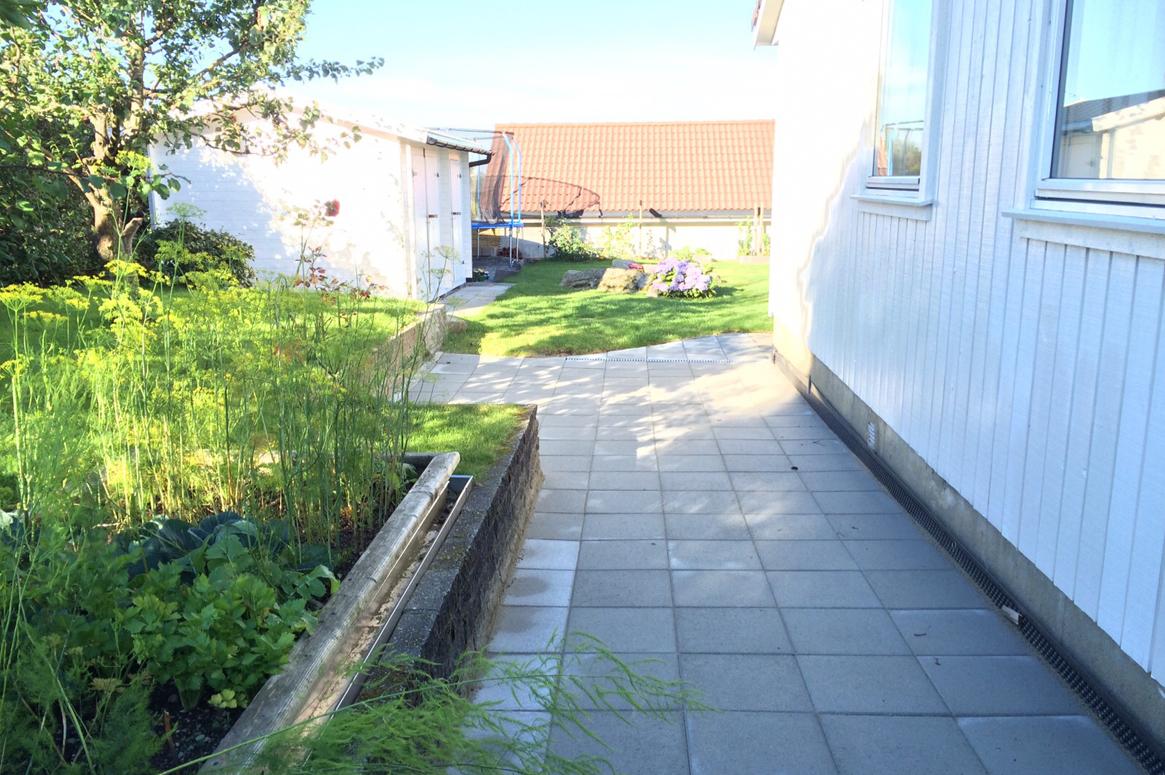 4 Seasons Garden. Korridoren på sørsiden av huset definerer frukthagen med tilhørende arbeidsbod for oppbevaring.