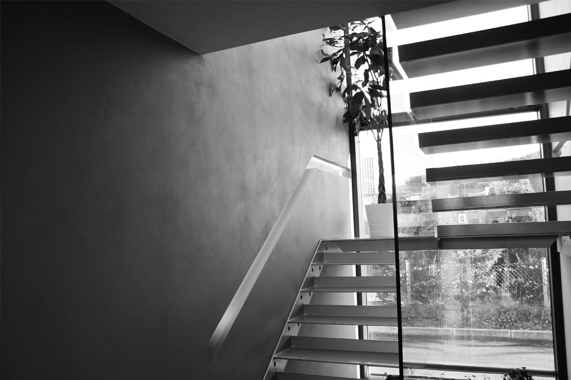 Glass rekkverk, ståltrapp, betongvegger , innfelt belysning.