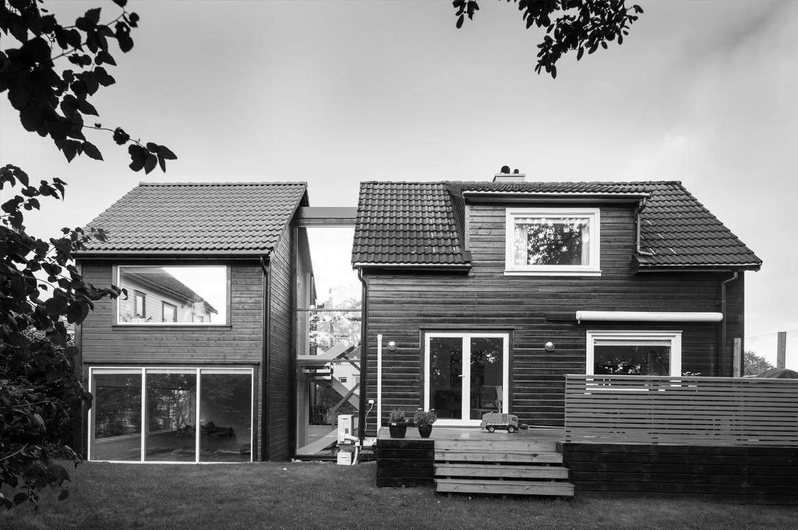 Fasaden åpnes opp mot hagen. Terrassen utenfor kjøkken og allrom absorberer høydeforskjeller i hagen.